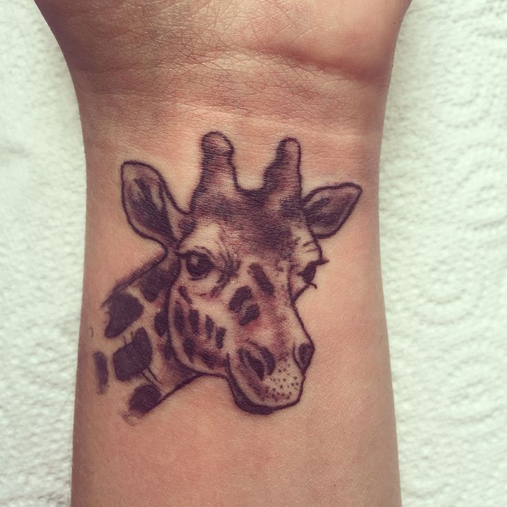 Small, girly, giraffe tattoo on wrist. In black and white