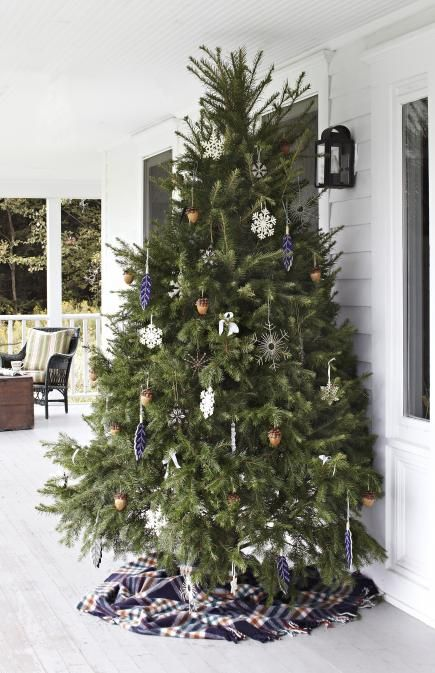 Extend your decorating outside by putting a tree on the porch. A plaid blanket becomes a quaint tree skirt. Click for more creative Christmas tree ideas.