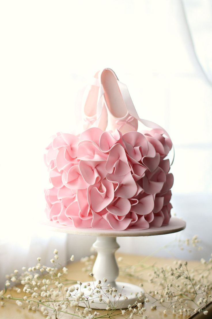 Super pretty ballet birthday cake with pink ruffles and ballet shoe cake topper.