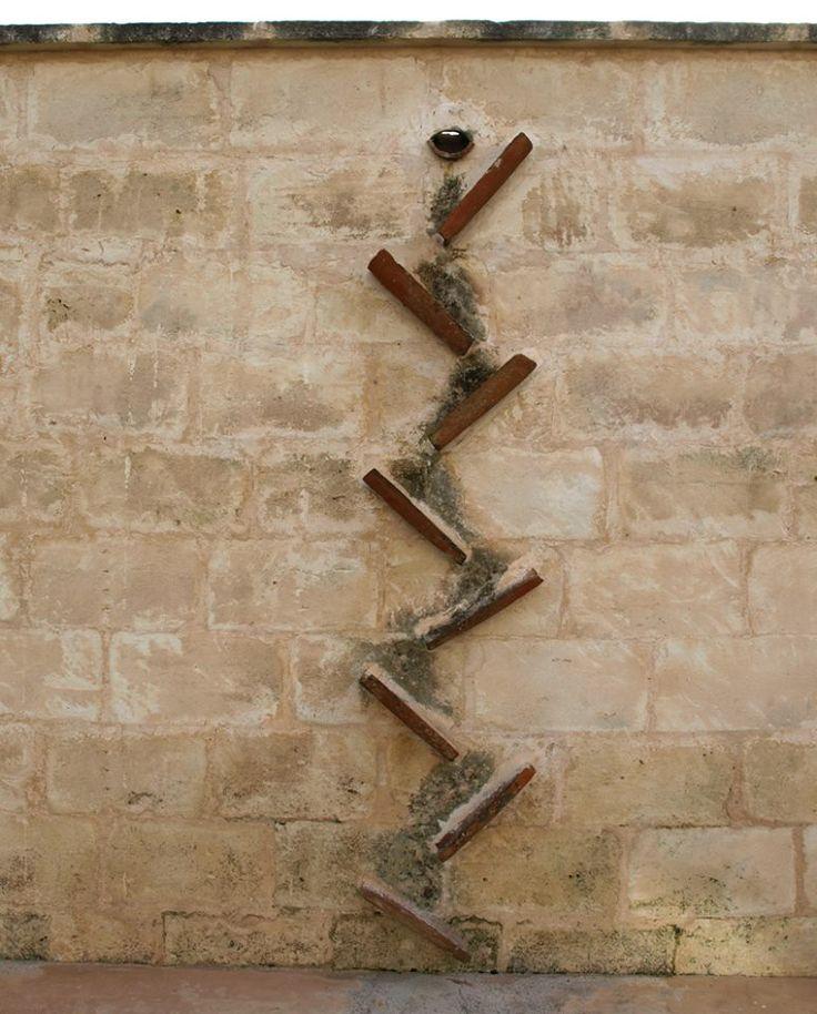 Cascada de tejas en un muro de piedra de Marés