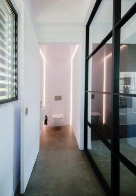 Minimalistic industrial toilet / loo design. The back wall beholds blind doors to put away all little requisites and also contains integrated LED-lighting to enhance and accentuate the vertical lining of the steel glass wall. Execution and design by Interi-Art Maatwerk Interieurs