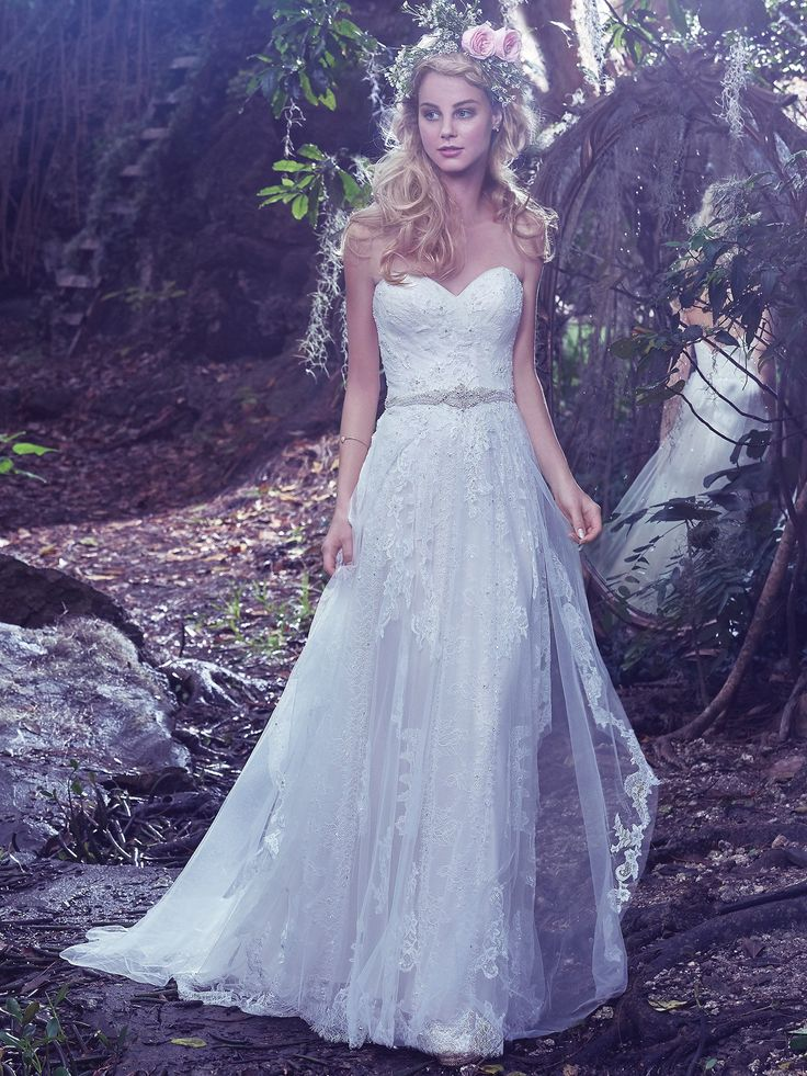 Understated elegance is found in this romantic sheath wedding dress featuring layers of tulle, adorned with Swarovski crystals, pearls, and lace appliqués. A glimmering beaded belt and sweetheart neckline, add touches of refined femininity. Finished with covered buttons over zipper closure. Bailey by Maggie Sottero