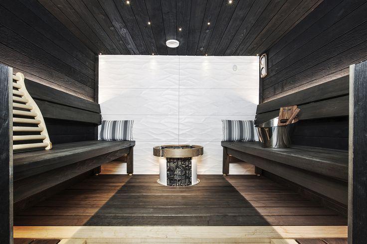 The black and white sauna interior in Finland. White color is repeated in the back wall and outer casig of the heater. #blackandwhite #saunadesign #saunainterior #citysauna