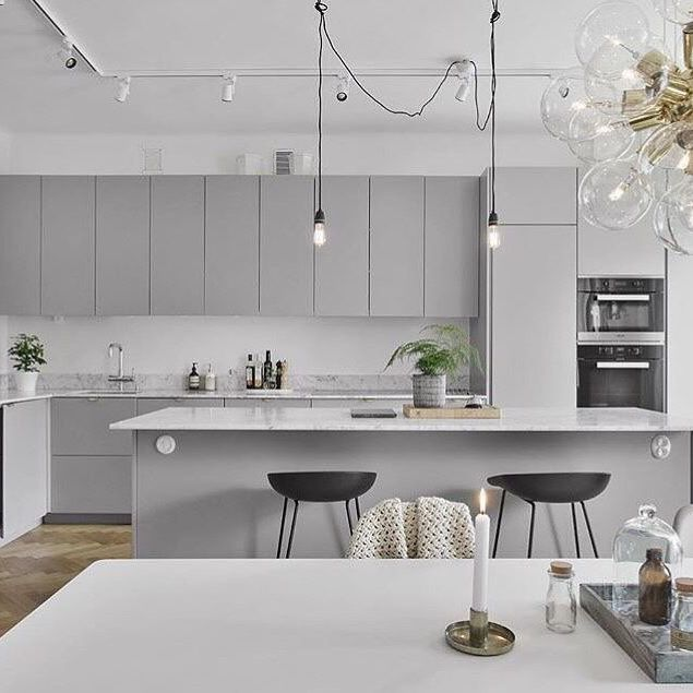 I was certain I wanted white but now I'm thinking light grey cabinetry for my next kitchen, doesn't it look great with the marble benchtops and black + brass accents @visionmakleri