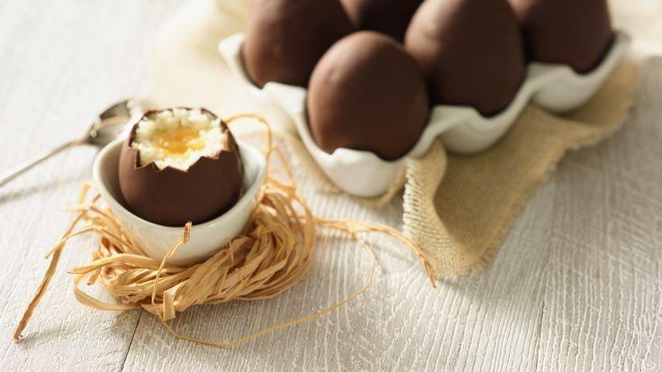 Mixez les abricots. Garnissez 4 alvéoles d'un bac à glaçons avec la préparation puis placez au congélateur 2 heures. Mélangez la noix de coco et le lait concentré. Démoulez les glaçons d'abricots et coupez-les en deux. Formez des œufs avec la pâte de noix de coco autour de chaque glaçon. Déposez-les en aplatissant légèrement la base. Placez-les au congélateur 30 minutes. Enfoncez un pic dans les œufs pour les tremper dans le chocolat. Retirez les pics et placez-les au réfrigérateur 30…