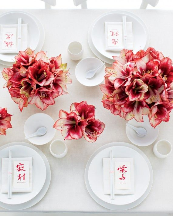 """Take the mantra """"less is more"""" to heart and let a single flower shine. Choose a captivating but affordable bloom from your bouquet, like these 'Showmaster' amaryllis, then cluster the stems in various-size vessels strewn across your tables. You'll find that there's beauty in minimalism -- and repetition.Calligraphy by Masako Inkyo (masako-inkyo.com)."""