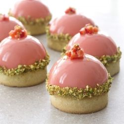 Pistachio tartlette with strawberry mousse dome.