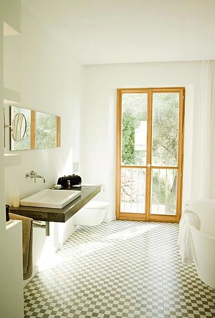 Beautiful door style windows with a chequered floor. Light and relaxing bathroom