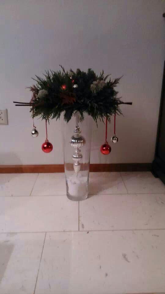 kerststuk op glazen vaas met een piek in de vaas gehangen