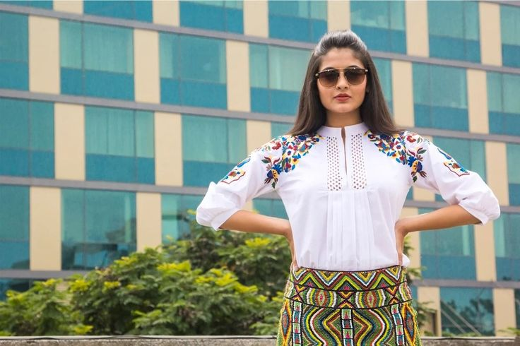 White blouse with pleated middle and floral sleeve embroidery, styled with a African patterned high waisted skirt by Bayside Blue