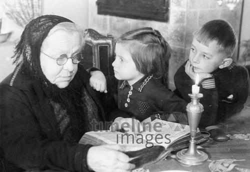 Großmutter und Enkelkinder, 1941 Timeline Classics/Timeline Images #1940er #1940ies #großmutter #kerze #vorlesen #Oma #Enkelkinder #Mädchen #Junge #historisch #historical #schwarzweiß