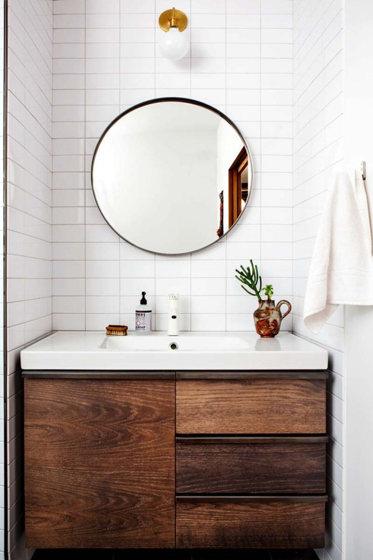 White tiled bathroom with wood cabinet sink