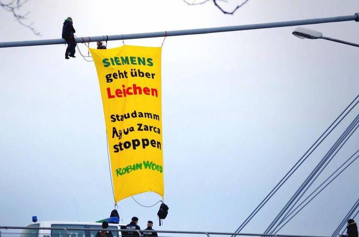 """Siemens gegen Menschen/ Siemens against Humans-""""An den Aktien und Profiten von Siemens klebt Blut. Das Kraftwerk Agua Zarca steht exemplarisch für eine Konzernpolitik, die über Leichen geht. Wir fordern die AktionärInnen auf, den Vorstand zur Verantwortung zu ziehen und eine Firmenpolitik durchzusetzen, die sowohl auf Umweltschutz als auch auf Menschenrechten beruht."""""""
