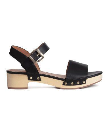 Sandalen aus Lederimitat. Knöchelriemen mit verstellbarer Metallschnalle. Innensohle aus Lederimitat. Laufsohle aus Holzimitat und Gummi. Plateau vorn 2,5 cm, Absatz 4,5 cm.