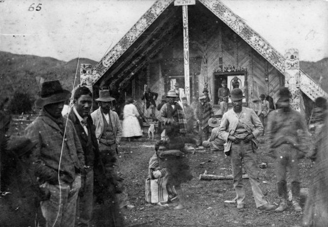 Unidentified group alongside the Te Tokanganui-A-Noho meeting house in Te Kuiti, ca 1900. #Maori