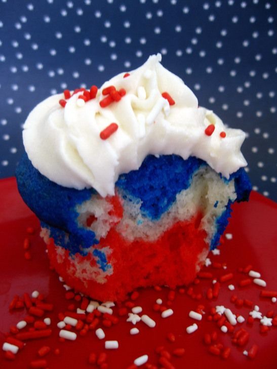 These intensely colored 4th of July cupcakes are sooo easy!  Prepare a box of white cake mix batter, divide into 3 bowls, tint with Wilton food color gels, layer batters and bake as directed on box.  Top with your favorite frosting and sprinkles.