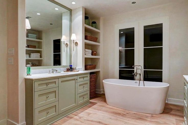 Cottage bathroom features a gray green vanity topped with carrera marble under a gray green framed ...