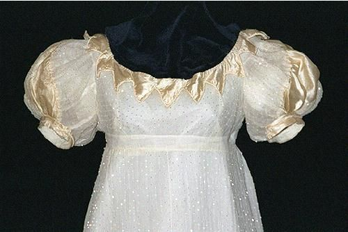This is an original ballgown from 1818. Note the beaded fabric and gold trim details. The sleeves are very large, which points to the late Regency period.