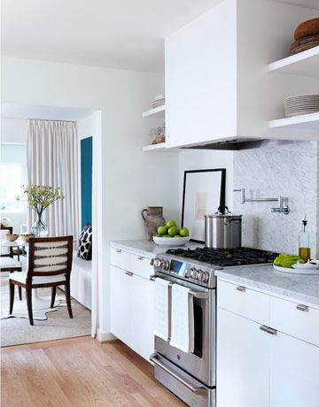 """Open shelves in the galley-style kitchen """"keep everything right at hand,"""" Bond says.   - HouseBeautiful.com"""