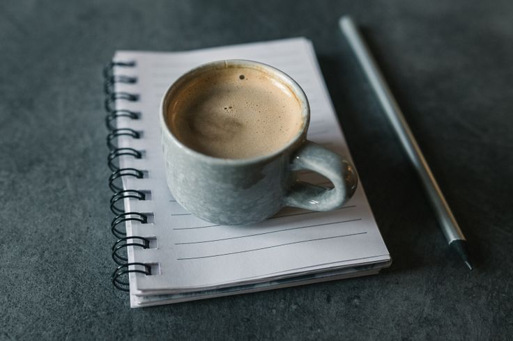 Cup of coffee on a empty notepad