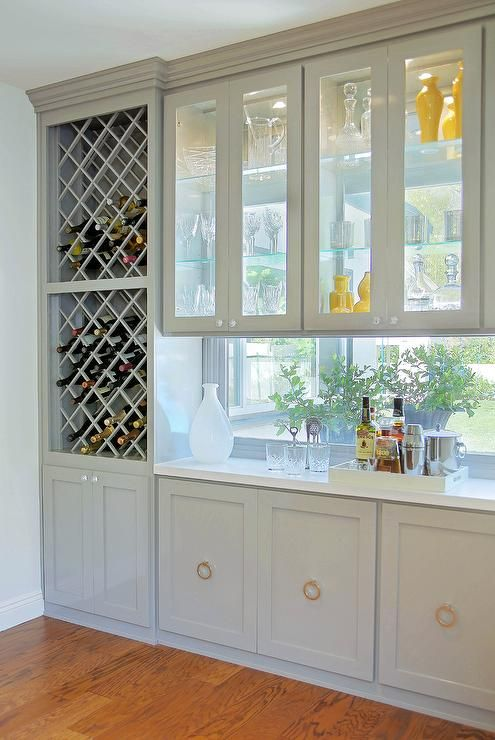 Gorgeous kitchen bar features stacked cross cut built in wine racks placed next to see through cabinets, with view to backyard, over a framed window backsplash and gray cabinets adorned with ring pulls.