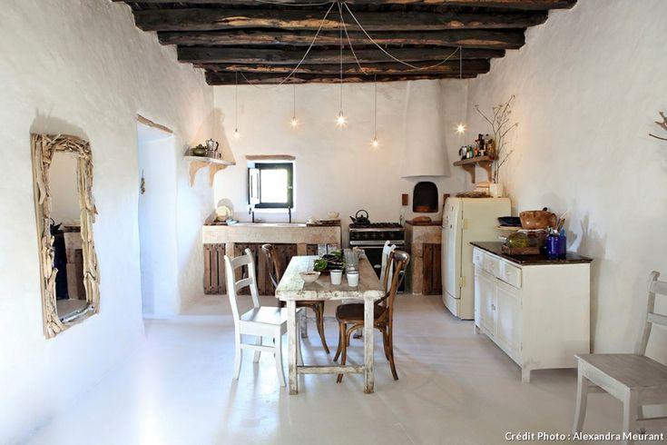 Dans la cuisine de cette maison aux Baléares, le blanc domine. Quelques étagères ajoutent une touche de modernité à cette pièce au décor rustique. Gobelets signés Baan.
