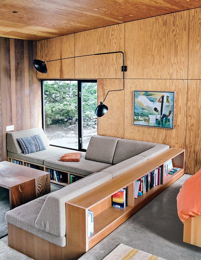 built in sofa with storage --  plywood wall --  The guesthouse has similar built-ins and is outfitted with a reproduction rotating sconce by Serge Mouille and rugs by Stephanie Odegard. --  Interior of a modern guesthouse in Sea Ranch with comfortable built-ins