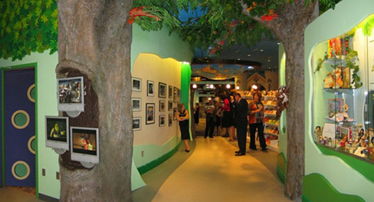 Tree Trail lined with display cases, tack board wall and information screens at The Trove (White Plains Public Library children's rooms)