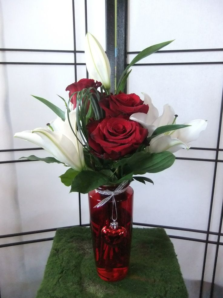 Cherish-white lily, 5 red roses, bear grass & salal in red vase with heart detail