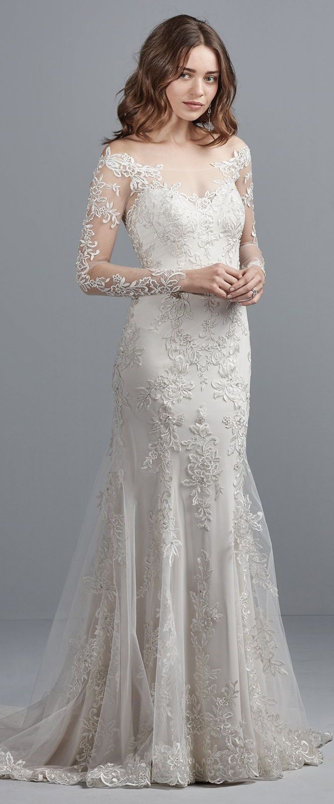Beaded lace appliqués and Swarovski crystals cascade over a layer of Inessa Jersey in this off-the-shoulder wedding dress, featuring illusion long sleeves, illusion bateau over sweetheart neckline, and illusion scoop back in a sheath silhouette. Finished with crystal buttons over zipper closure.