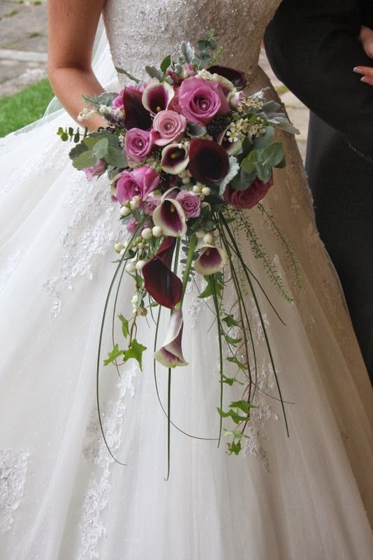 magnificent cascading Bridal Bouquet of Roses, Calla Lilies, Lily of the Valley, Wax Flower Blossom, Senecio and Ivy looked just perfec