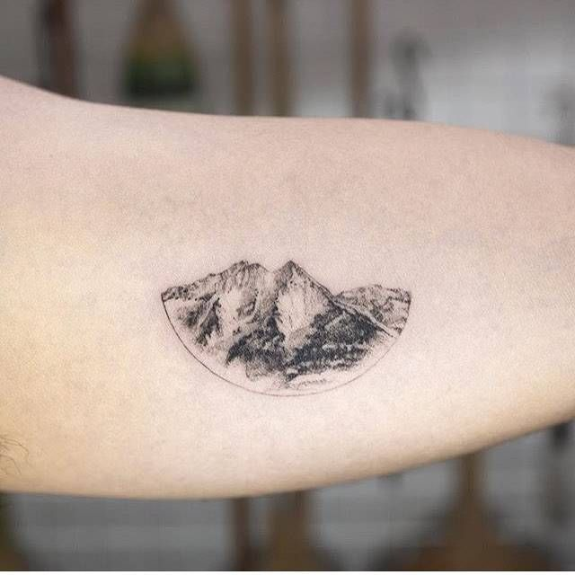 Single needle mountain range tattoo on the left inner arm.