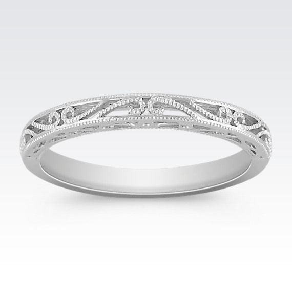 This charming wedding band is crafted in quality 14 karat white gold.  The milgrain detailing gives the design a vintage feel.