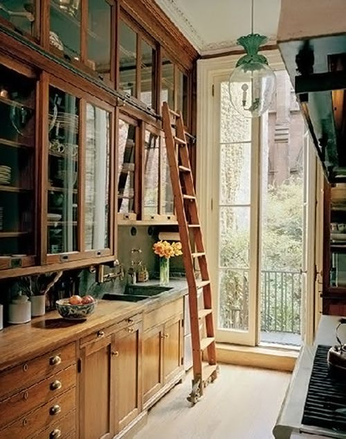 A galley kitchen makes great use of space with floor-to-ceiling natural-wood cabinets, a rolling library ladder, and French doors that let the light in.