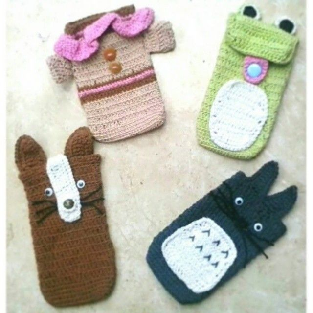 crochet phone cases. (clockwise) its a cute crochet shirt phone case, crochet frog phone case, totoro from ghibli studio Japan crochet phone case, and I'm not sure about it lol but its a crochet cat phone case :)