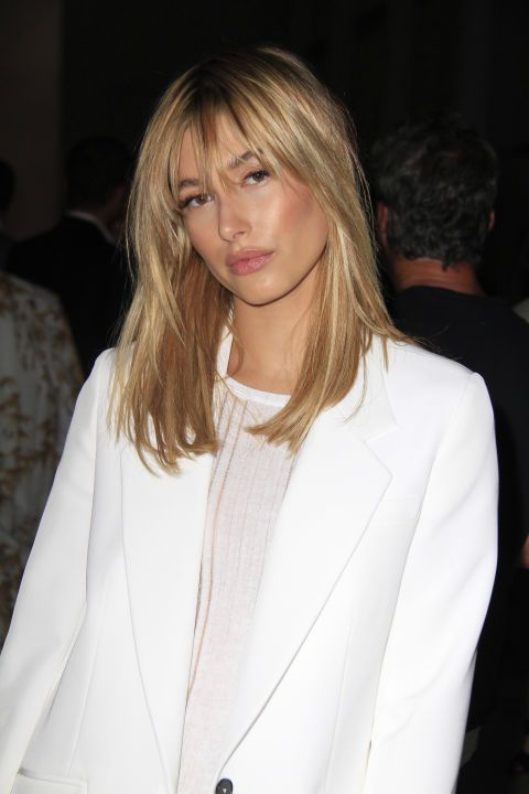 Hailey Baldwin styles her medium length hair with breezy bangs and long layered …
