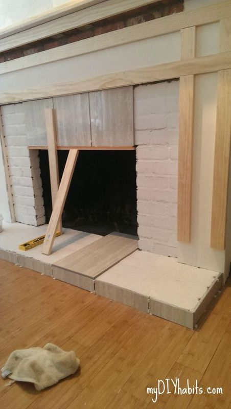 diy brick fireplace refacing, concrete masonry, concrete countertops, diy, fireplaces mantels, how to, living room ideas, Step 3 Tile Continued Start from the top middle and work your way around Use a piece of wood to counter act gravity