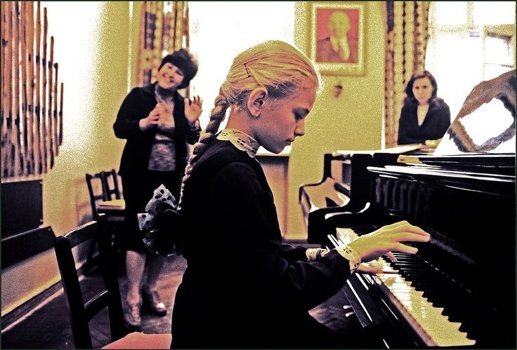 Ukraine. Odessa. A young girl playing the piano under instruction at the famous Stolyarsky Music School with a portrait of Lenin on the wall. 1982
