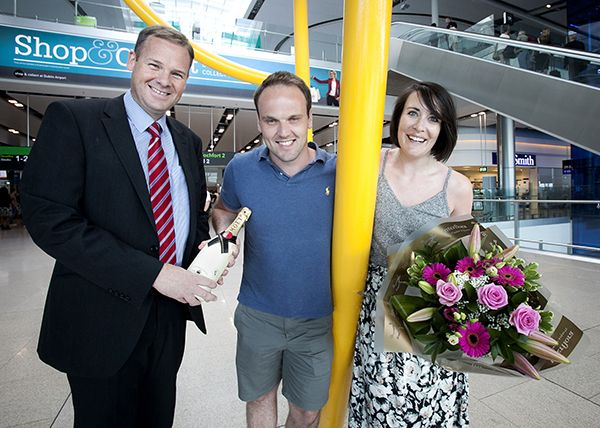 Bank Holiday Weekend caps busiest July ever at Dublin Airport. Image show Dublin Airport head of operations Gary McLean presenting passengers Mark Owen and Laura Walsh with champagne, flowers and chocolates. Laura was the 2.5 millionth passenger to use the airport in July
