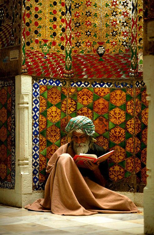 INDIA:  holy man in meditative reading... against the beauty of Indian tapestry.