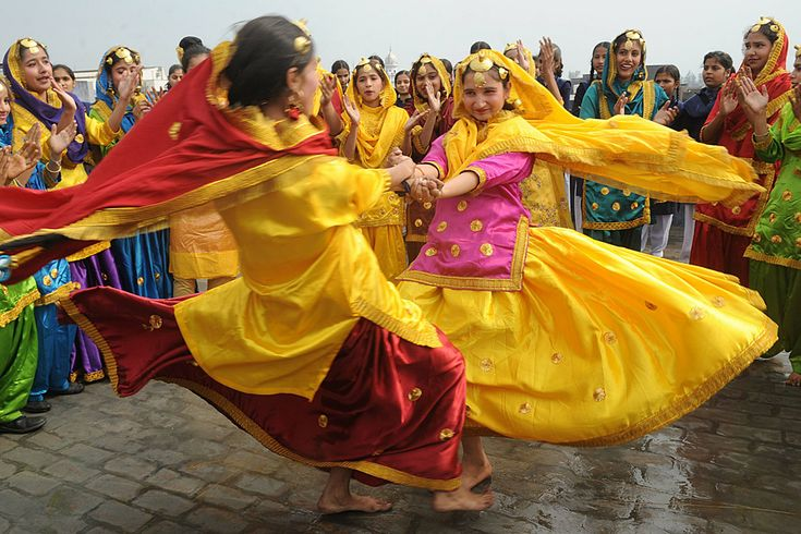 Indian school girls spin in a swirl of color on the eve of Basant Panchami, the Festival of Spring, in Amritsar