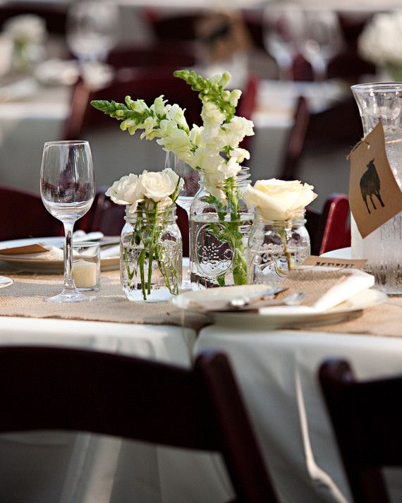Centerpieces were kept minimal at this Midwest wedding reception so they wouldn't detract from the natural surroundings. Jars filled with white stock flowers and roses were placed in small groupings down the tables.
