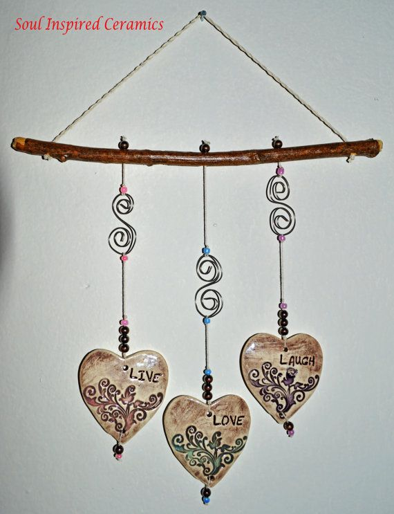 """This wind chime is made out of three large ceramic hearts (approximately 3'' in size) with the words """"Live, Love, Laugh"""" carefully stamped on each one of them! Each heart is colored in brown glaze and a little bit of pink, turquoise and purple glaze to make a beautiful accent on the piece. They are then attached carefully to the wooden stick using some tiny beads. The wire spirals add the finishing touch on this beautiful mobile!  #ceramicmobile #windchime #livelaughlove"""