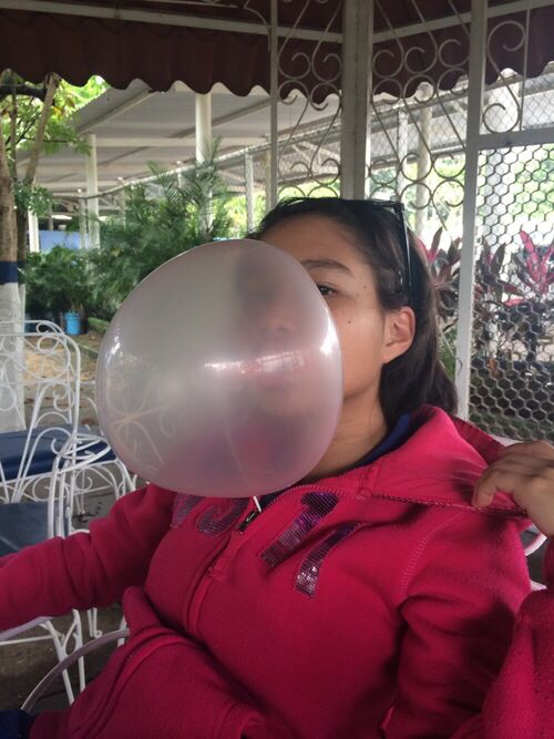 Girl Blowing A Huge Bubble With Pink Bubble Gum Bubble