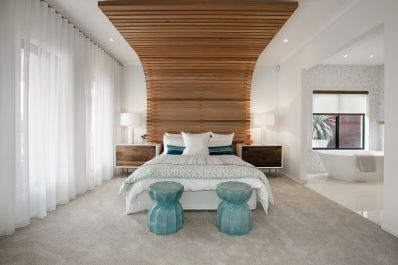 This uber cool master bedroom has a mixture of contemporary glam and vintage deco feel. White walls, vibrant blue linen, light timber bedside tables and timber feature wall fill this room. As displayed in Dunes 33 at Williams Landing Estate.