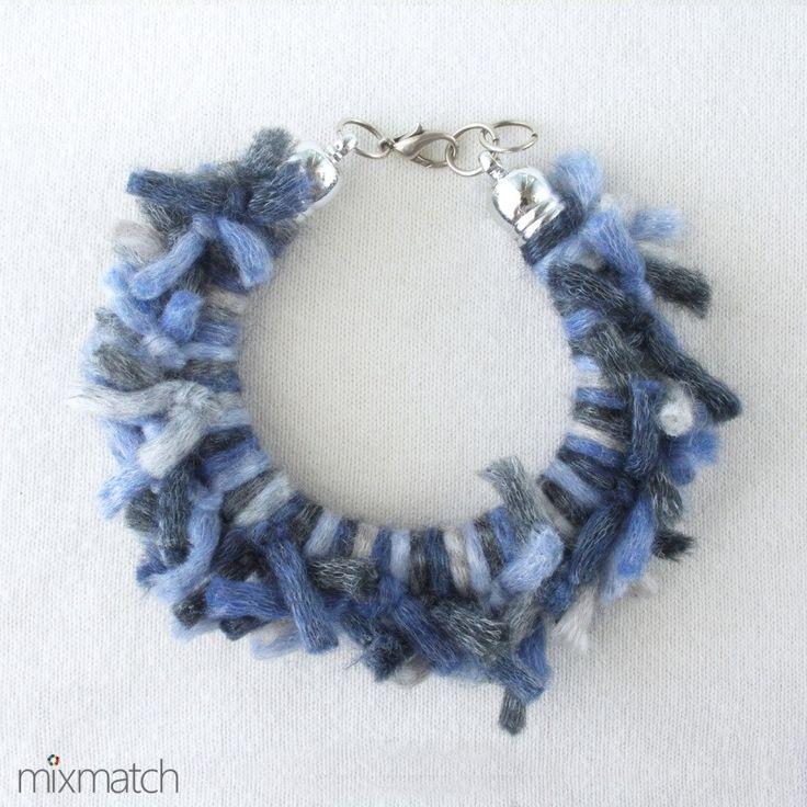Βραχιόλι με κόμπους από ακρυλικό νήμα σε μπλε και γκρι αποχρώσεις και ακρυλικό επιμεταλλωμένο κούμπωμα σε ασημένιο χρώμα.