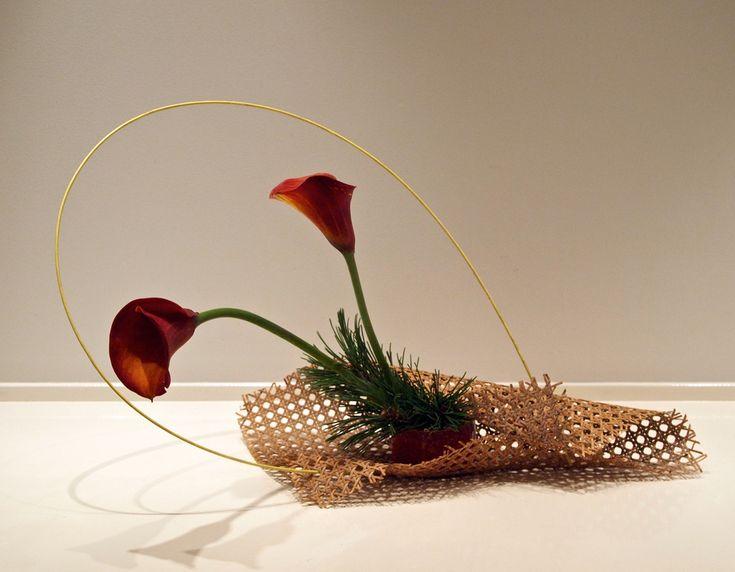 Modern basket ikebana. Calla lily, pine and bamboo stick.