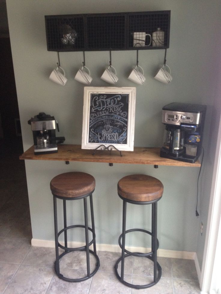 DIY coffee bar: 1x12 lumber stained to match kitchen cabinets and mounted to the wall with brackets; hand-made coffee chalkboard; hanging wire cabinet/shelf with coffee cup hooks: Home Goods; bar stools: Home Goods; paint color: Sherwin Williams comfort gray.
