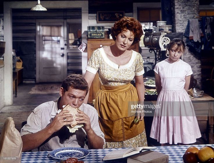 James MacArthur eats as Maureen O'Hara looks over him in a scene from the film 'Spencer's Mountain', 1963.