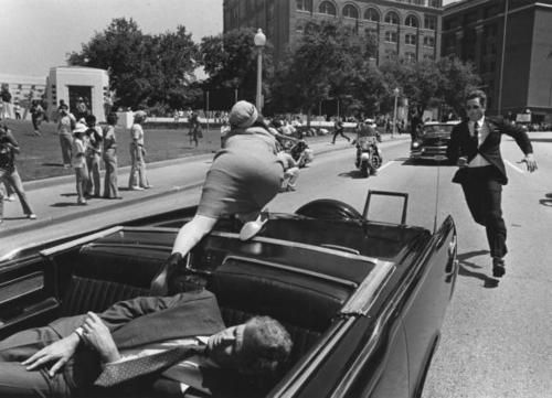 Debunked: A photo allegedly shows a closeup of Jackie Kennedy climbing on the back of the limousine with John F. Kennedy slumped in the seat behind her.